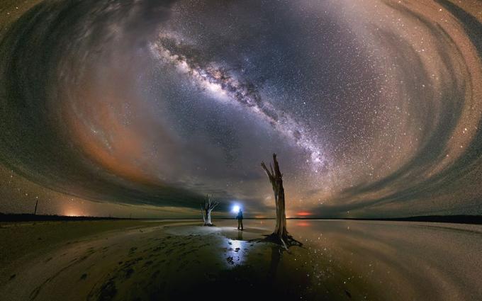 Selfies com o Espaço O fotógrafo Michael Goh imortalizou as estrelas  de noite australianas no parque nacional de Nambung ,na parte ocidental do país. As belas imagens mostram o céu noturno repleto de miglaia de estrelas  da bela Via Láctea. As fotografias são tiradas com uma exposição de 30 minutos. O fotógrafo de 45 anos, que visitou vários lagos de sal, utiliza várias técnicas e retrai nas paisagens escolhidas com uma câmera de controle remoto. Em Nambung Parque,  ele conseguiu capturar o efeito de espelho do lago de sal que reflete o espetáculo do céu estrelado. Na Via Láctea, a galáxia que contém o nosso sistema solar, existem 400 bilhões de estrelas. Estas últimas, gases, poeira e planetas fazem da  Via Láctea um espetáculo único.Fotos ©Fotodom.ru/Rex Features