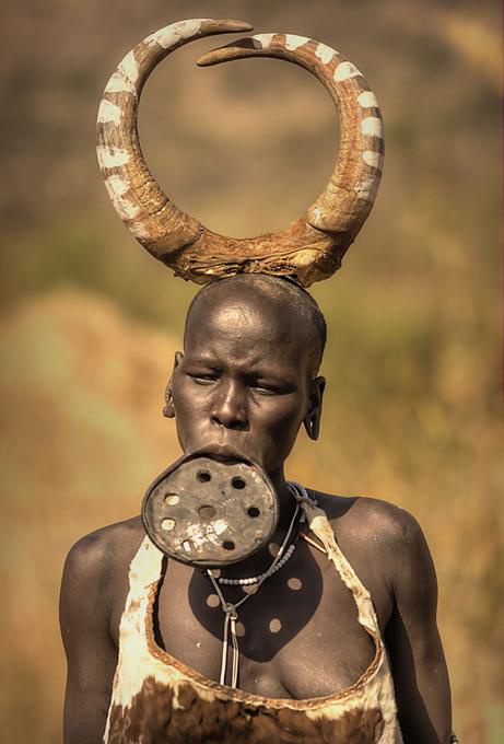 Meninas belas da tribo Mursi Na tribo Mursi, na Etiópia é costume as mulheres utilizarem discos de madeira nos lábios inferiores, a partir dos 15/16 anos. Estes indígenas vivem principalmente do pastoreio de grandes rebanhos de gado no vale do Omo, se dedicam à agricultura de cereais, sorgo, milho e sobretudo são coletores de mel. Calcula-se que restam uns 9.000 indígenas Mursi. ©Fotodom.ru/Rex Features