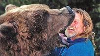 """Doug Seus aos 71 anos  é um dos treinadores de ursos mais conhecidos de Hollywood. Fez um vídeo onde brinca com um urso-pardo com mais de dois metros. Nas imagens pode ver-se a confiança que Doug tem no animal que até põe a cabeça dentro da boca do urso, sabendo que uma única mordidela pode ser fatal. Fotos Splash/All Over  Doug vive com a sua mulher, Lynne, no Utah, onde passa longas horas a conhecer e a treinar os ursos. """"Gastamos horas com eles. Não ensinamos truques mas chegamos-lhes ao coração, à alma"""", diz o treinador.  O casal tem três ursos treinados. O Bart Two, o Henoybump e o protagonista do vídeo, Tank, que já foi visto pelo mundo na série Guerra dos Tronos. Os ursos da família de Doug Seus já contracenaram com actores como Brad Pitt e Morgan Freeman."""