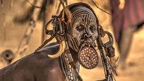Na tribo Mursi, na Etiópia é costume as mulheres utilizarem discos de madeira nos lábios inferiores, a partir dos 15/16 anos. Estes indígenas vivem principalmente do pastoreio de grandes rebanhos de gado no vale do Omo, se dedicam à agricultura de cereais, sorgo, milho e sobretudo são coletores de mel. Calcula-se que restam uns 9.000 indígenas Mursi. ©Fotodom.ru/Rex Features